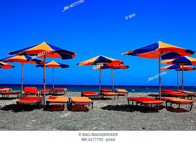Colourful beach chairs and umbrellas on beach, blue sea, Crete, Greece