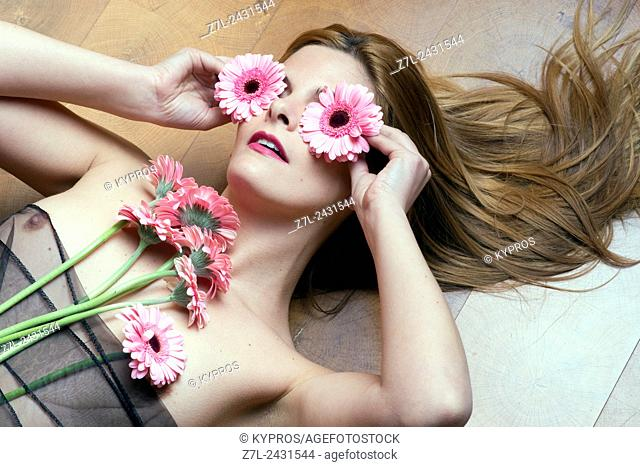 Young Woman Lying On Wooden Floor With Flowers