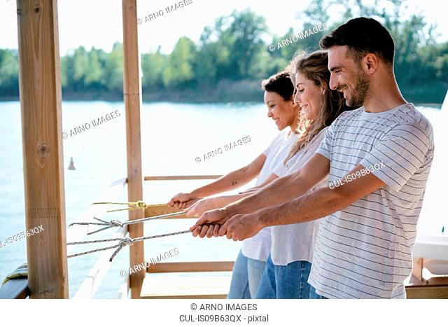 Three friends on pier, pulling on ropes with nautical knots