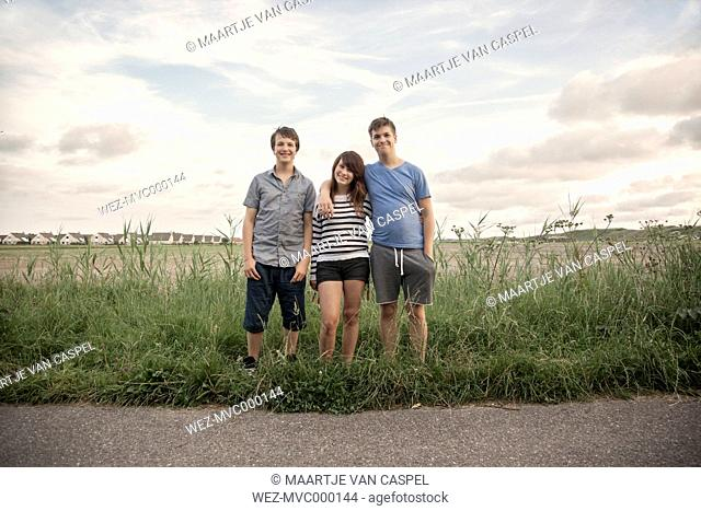Netherlands, three smiling teenagers standing in a row on wayside