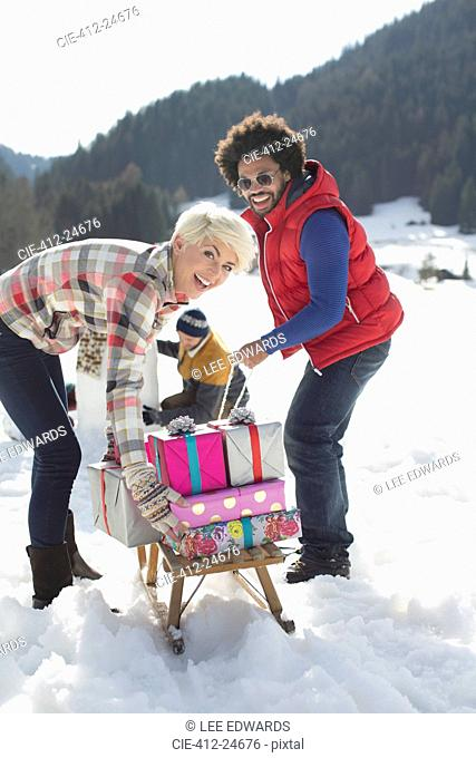 Portrait of couple with sled and Christmas gifts in snow