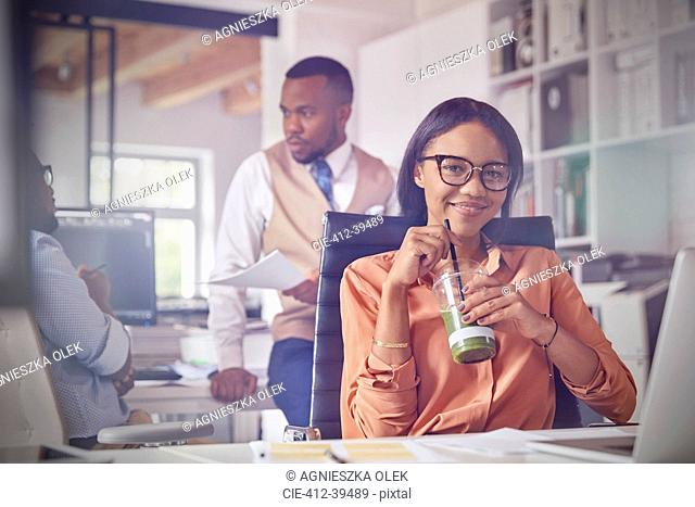 Portrait smiling confident businesswoman drinking green smoothie in office