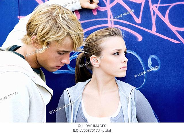Young teenage couple in front of a graffiti covered wall