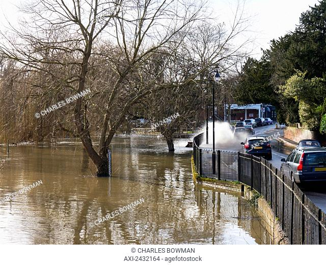 Flood water splashing on the road; Cobham, Surrey, England