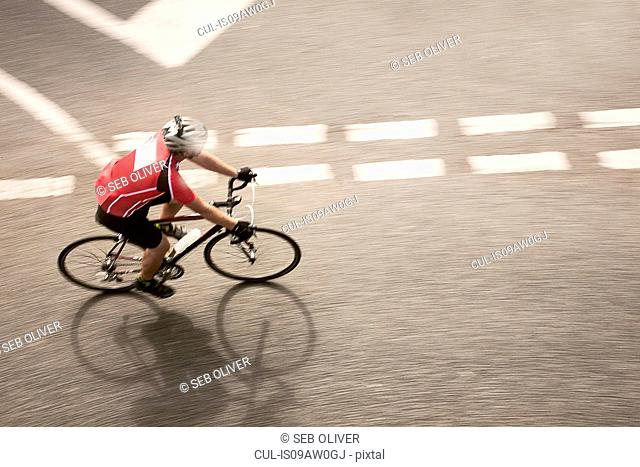 Overhead view of cyclist speeding on urban road in racing cycle race
