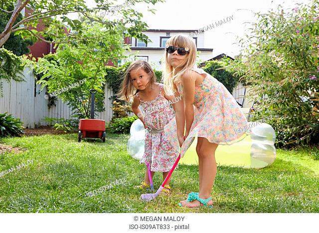 Girls playing kids golf in garden