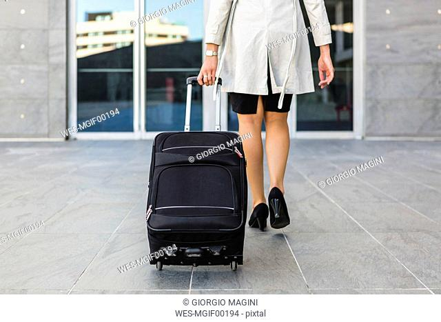 Back view of walking businesswoman with rolling suitcase