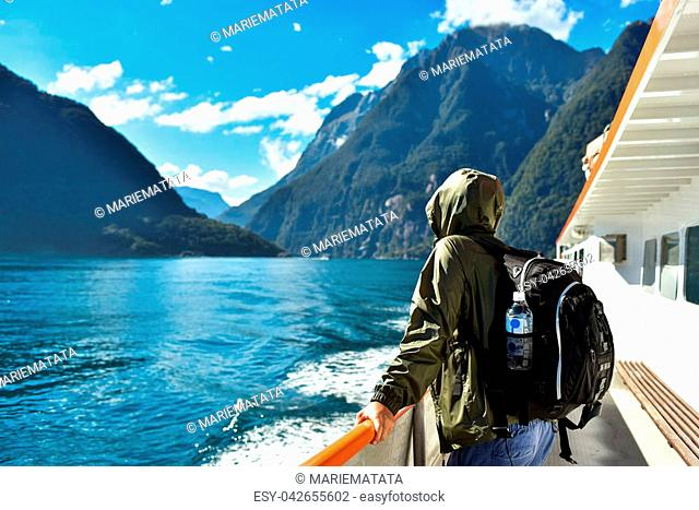 Man in a jacket holding a backpack with a bottle of water, standing on a boat deck and travelling along Milford Sound fiord in New Zealand