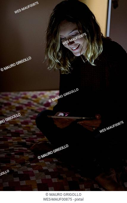 Woman sitting on bed at night using tablet
