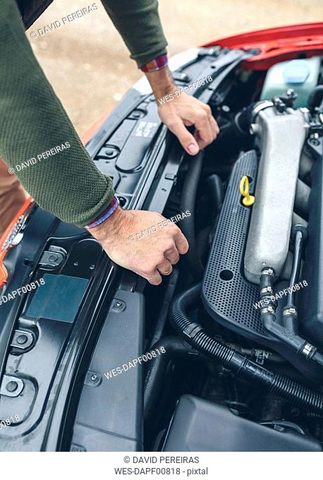 Close-up of man checking car engine