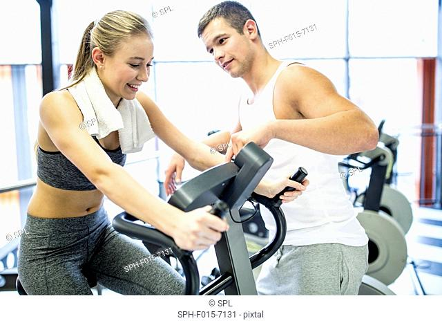 MODEL RELEASED. Man instructing woman to use exercise bike in gym, smiling