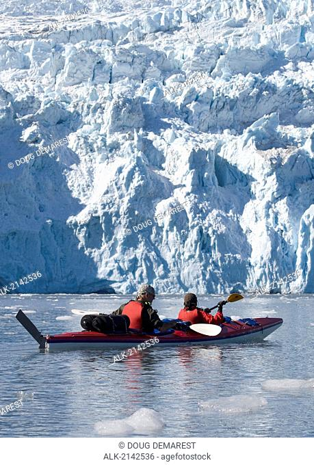 Tandem Sea Kayakers Near Moraine Of Aialik Glacier In Southcentral, Alaska During Summer