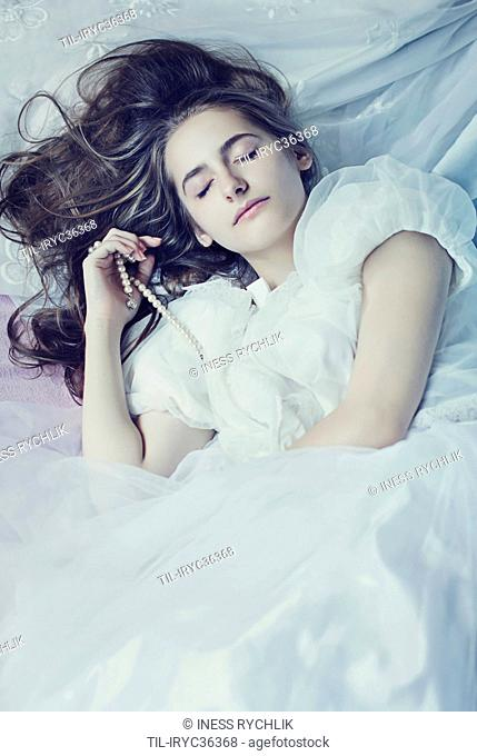 A portrait of a young long-haired female sleeping in a white tulle dress holding a pearl necklace in her hand