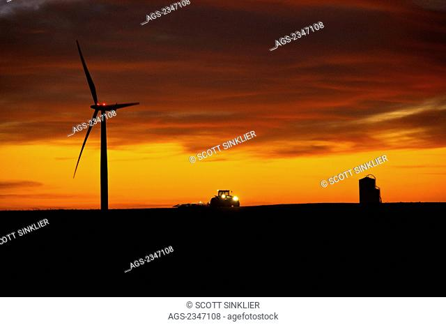 Agriculture - A farmer tills his field at dusk after corn harvest in late Autumn, below an electric wind turbine, illustrating the coexistence of traditional...