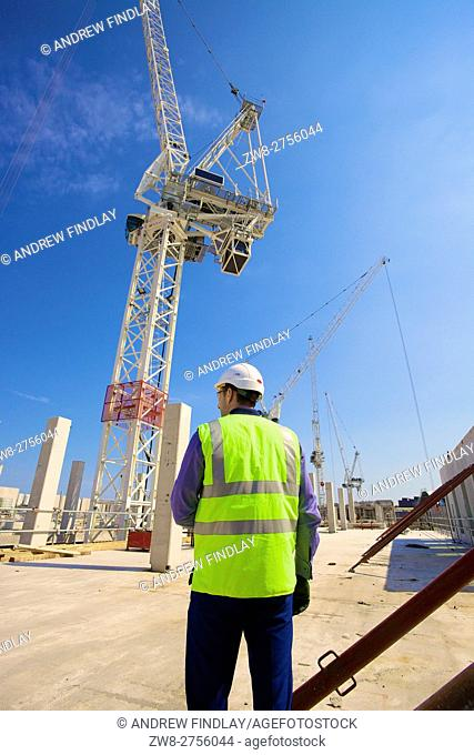 Worker wearing safety clothing watching construction using tower cranes