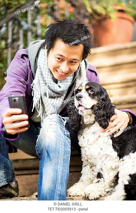 Teenage boy(16-17) taking picture of his dog