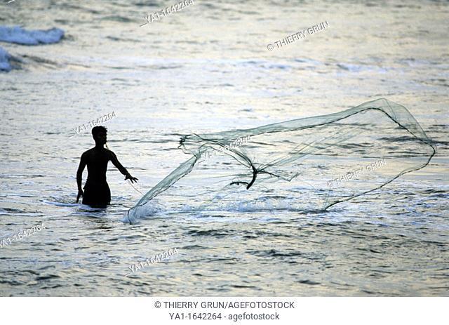 Local fisherman using a cast net in sea at dusk, Kalutara beach, Sri Lanka