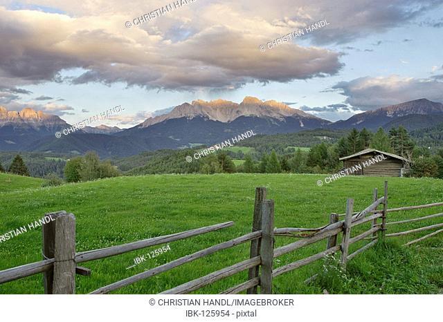 Wooden hut on a meadow behind the mountain range Latemar, Deutschnofen, Eggen valley, South Tyrol, Italy