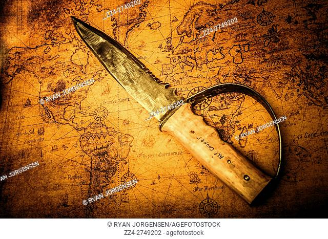Century old plunder and looting conceptual still life with a seafaring knife sitting on hidden treasures map. Nautical pirate details