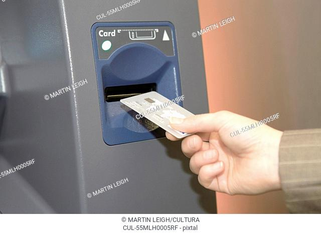 Woman inserting credit card into cashpoint