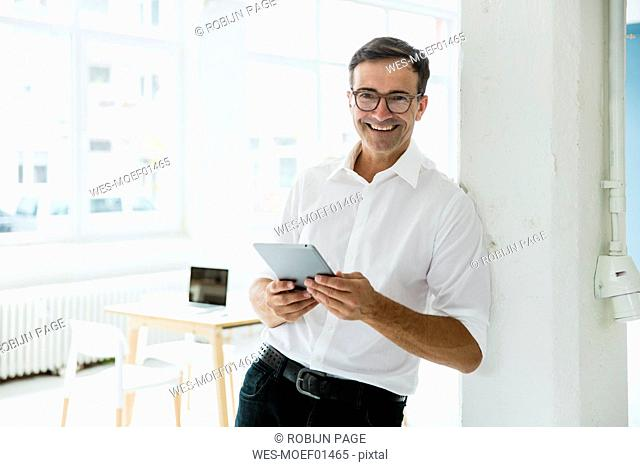 Portrait of happy businessman with tablet in bright office