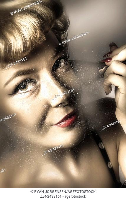 Dark creative photo of a beautiful girl looking in the mirror and applying blush powder cosmetics to cheekbones with a big make up brush