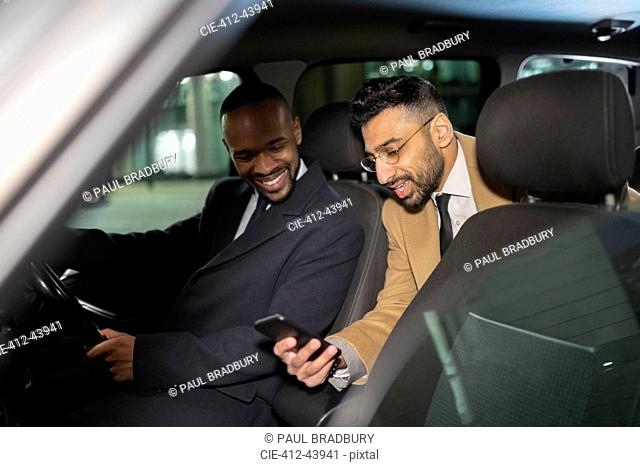 Businessman with smart phone using crowdsourced taxi