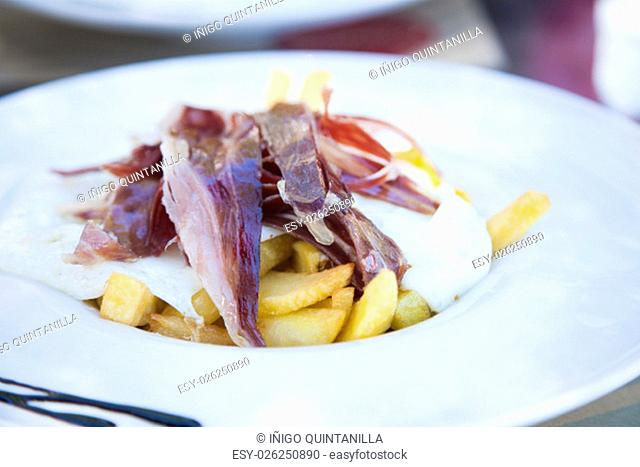 still life of white dish with typical Spain food named huevos rotos or broken eggs with potatoes french fries fried eggs and slices of iberico ham on table at...