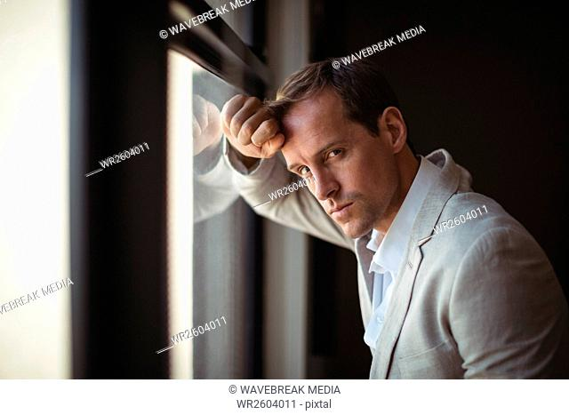 Thoughtful businessman leaning on window