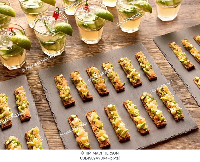 Guacamole, smoked salmon and rye bread canapes with vodka cocktail garnished with lime wedges