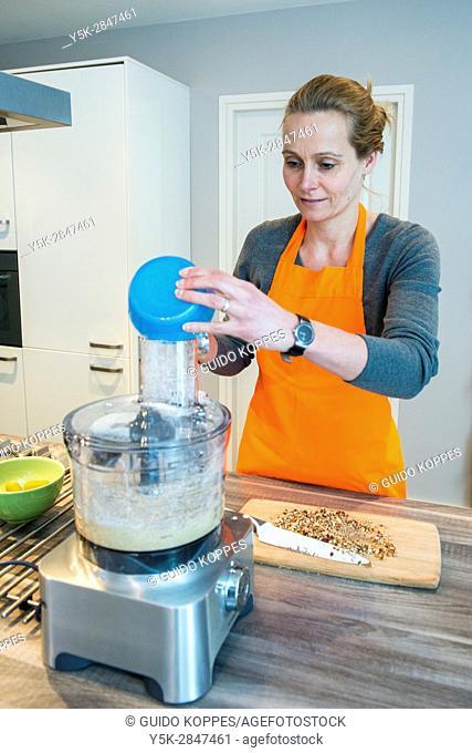Kaatsheuvel, Netherlands. Mid adult caucasian woman preparing to bake a cake inside her residential kitchen
