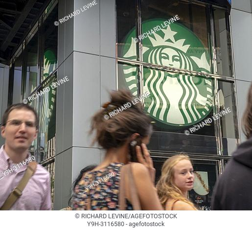 Passer-by walk past a Starbucks coffee shop in Midtown Manhattan in New York on Tuesday, July 24, 2018. (© Richard B. Levine)