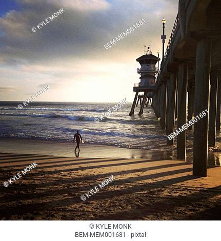 Surfer walking under wooden pier on beach