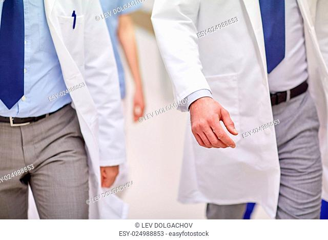 clinic, profession, people, healthcare and medicine concept - close up of medics or doctors walking along hospital