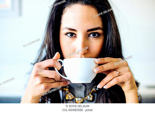 Portrait of young woman drinking coffee in boutique hotel in Italy