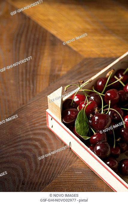 Red Cherries in Crate on Wood Table