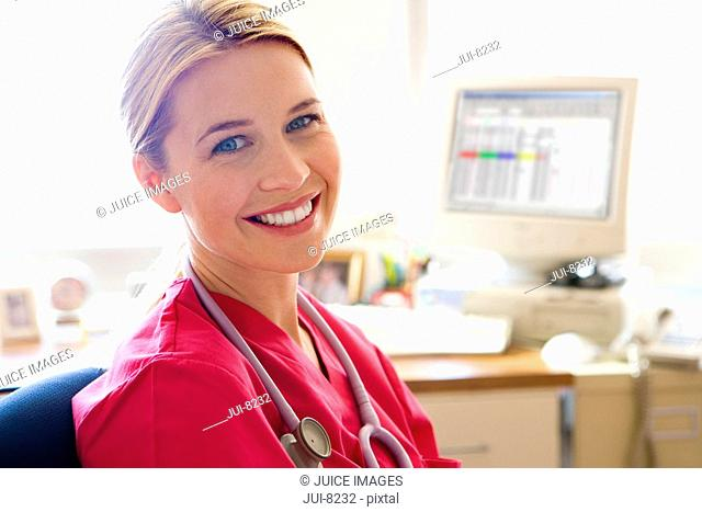 Young female nurse sitting by desk, smiling, portrait, close-up