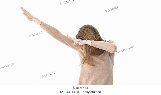 Young beautiful woman making DAB dance white wall background