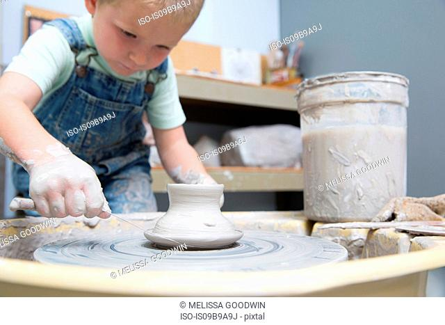 Boy cutting pot from potter's wheel