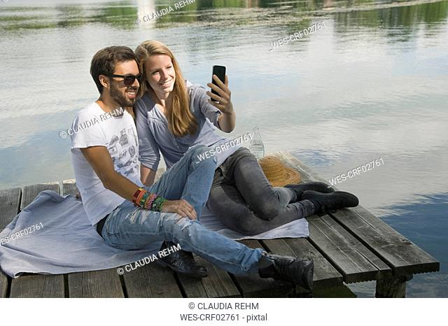 Smiling young couple sitting on jetty at a lake taking a selfie