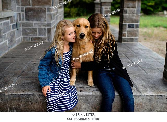 Girl and her sister sitting on patio hugging their golden retriever