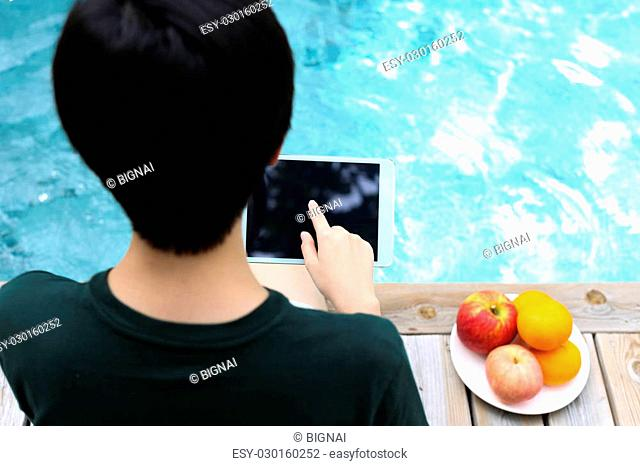 Asian people sitting by swimming pool using tablet computer with fresh fruit