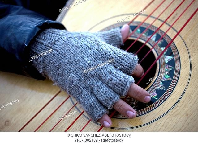 A man wearing wool gloves play the guitar outside of the Our Lady of Guadalupe Basilica, Mexico City, December 6, 2010  Hundreds of thousands of Mexican...