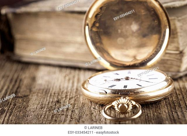 vintage pocket watch and book on wood still life closeup