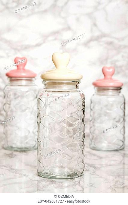 Empty glass jars on white marble background