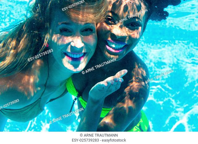 girlfriends diving in swimming pool underwater,black and white girl