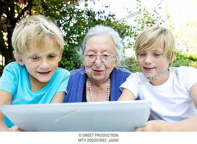 Grandmother and her two grandsons looking at tablet computer