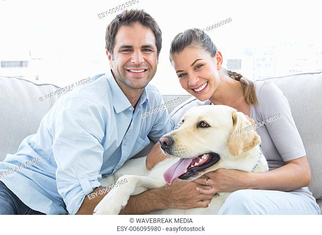 Smiling couple petting their yellow labrador on the couch