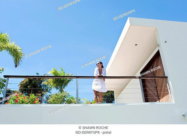 Young woman on apartment balcony in sunlight