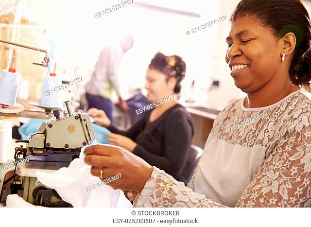 Smiling woman sewing at a community workshop, South Africa